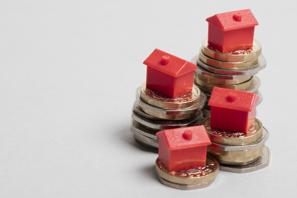 Toy houses on piles of money to signify homeowner loan