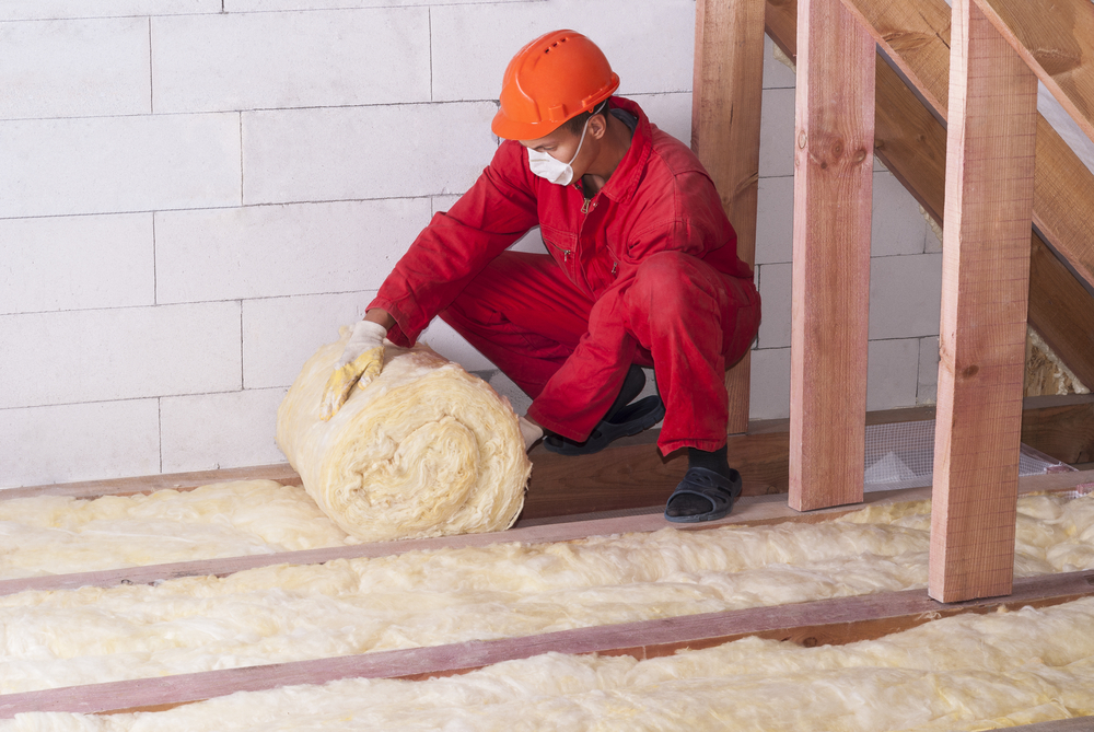 Man installing loft insulation for home improvements