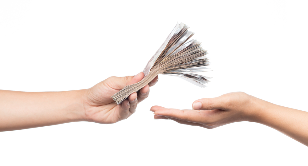 A hand presenting a pile of money from switching energy suppliers