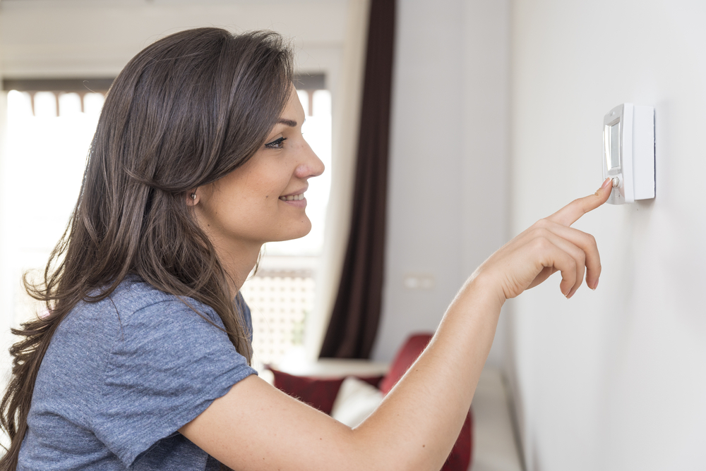 A woman pressing the thermostat in her home to save money