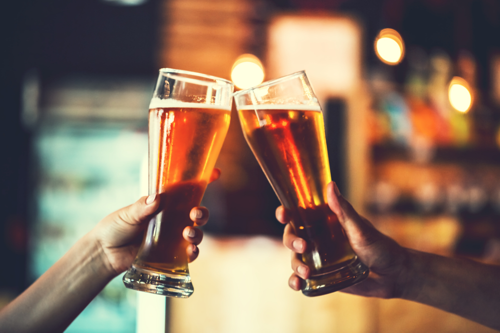 Two friends toasting with their pints of beer in the pub